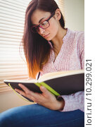 Купить «Pretty brunette studying beside window», фото № 10299021, снято 4 июня 2015 г. (c) Wavebreak Media / Фотобанк Лори