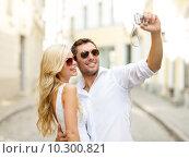 Купить «travelling couple taking photo picture with camera», фото № 10300821, снято 14 июля 2013 г. (c) Syda Productions / Фотобанк Лори
