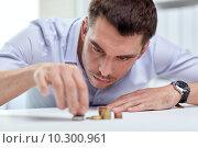 Купить «businessman with coins at office», фото № 10300961, снято 18 июня 2015 г. (c) Syda Productions / Фотобанк Лори