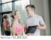 Купить «smiling young woman with personal trainer in gym», фото № 10305521, снято 29 июня 2014 г. (c) Syda Productions / Фотобанк Лори