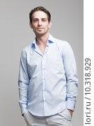 Купить «Молодой мужчина в голубой рубашке стоит на сером фоне», фото № 10318929, снято 9 июня 2015 г. (c) Дмитрий Булин / Фотобанк Лори