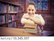 Купить «Blonde teacher leaning on pile of books in the library», фото № 10345397, снято 8 июля 2015 г. (c) Wavebreak Media / Фотобанк Лори