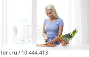 Купить «smiling young woman chopping carrot at home», видеоролик № 10444413, снято 1 мая 2015 г. (c) Syda Productions / Фотобанк Лори