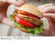 Купить «Мужские руки держат гамбургер», фото № 11070713, снято 21 августа 2015 г. (c) Лидия Рыженко / Фотобанк Лори