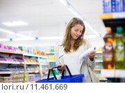 Купить «Beautiful young woman shopping in a grocery store/supermarket », фото № 11461669, снято 19 сентября 2018 г. (c) PantherMedia / Фотобанк Лори