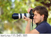 Купить «Photographer taking a photograph outdoor with a dslr camera», фото № 11541181, снято 19 октября 2018 г. (c) PantherMedia / Фотобанк Лори