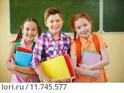 Купить «Small group of school friends looking at camera on background of blackboard», фото № 11745577, снято 15 декабря 2017 г. (c) PantherMedia / Фотобанк Лори