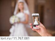Купить «Гость фотографирует невесту на мобильный телефон», фото № 11767081, снято 19 июля 2015 г. (c) Photobeauty / Фотобанк Лори