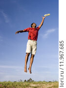 Купить «Man in red t-shirt and shorts jumping in air, hand raised, attempting to catch, low angle view», фото № 11967685, снято 16 декабря 2018 г. (c) PantherMedia / Фотобанк Лори