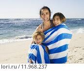Купить «Mother drying two daughters (5-12) with stripy blue towel on sandy beach, smiling, portrait», фото № 11968237, снято 13 декабря 2018 г. (c) PantherMedia / Фотобанк Лори