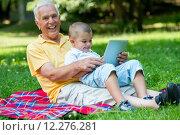 Купить «grandfather and child in park using tablet», фото № 12276281, снято 19 сентября 2019 г. (c) PantherMedia / Фотобанк Лори