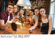 Купить «friends with smartphone on selfie stick at bar», фото № 12362097, снято 7 мая 2015 г. (c) Syda Productions / Фотобанк Лори