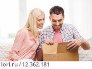 Купить «happy couple with parcel box at home», фото № 12362181, снято 6 июня 2015 г. (c) Syda Productions / Фотобанк Лори