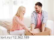 Купить «happy couple with open parcel box at home», фото № 12362189, снято 6 июня 2015 г. (c) Syda Productions / Фотобанк Лори