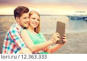 Купить «couple with tablet pc taking selfie over beach», фото № 12363333, снято 7 июля 2014 г. (c) Syda Productions / Фотобанк Лори