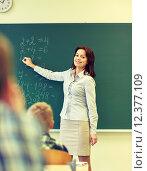 Купить «school kids and teacher writing on chalkboard», фото № 12377109, снято 15 ноября 2014 г. (c) Syda Productions / Фотобанк Лори