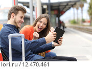 Купить «Euphoric couple playing games in a tablet in a train station», фото № 12470461, снято 26 мая 2018 г. (c) PantherMedia / Фотобанк Лори