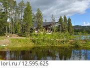 Купить «Северный пейзаж. Деревянный уютный коттедж среди деревьев на берегу озера на фоне сопок», фото № 12595625, снято 5 июля 2015 г. (c) Валерия Попова / Фотобанк Лори