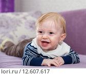 Портрет маленького улыбающегося ребенка, лежащего на животе. Стоковое фото, фотограф Дарья Филимонова / Фотобанк Лори