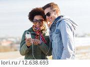 Купить «smiling couple with smartphone and earphones», фото № 12638693, снято 19 марта 2015 г. (c) Syda Productions / Фотобанк Лори