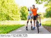 Купить «couple on rollerblades and bike showing thumbs up», фото № 12638725, снято 5 июля 2015 г. (c) Syda Productions / Фотобанк Лори