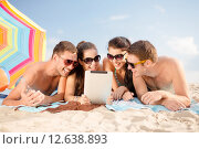 Купить «happy friends with tablet pc on beach», фото № 12638893, снято 31 августа 2013 г. (c) Syda Productions / Фотобанк Лори