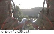 Влюбленные держаться за руки сидя в креслах в лучах заходящего солнца. Стоковое видео, видеограф Земсков Андрей  Владимирович / Фотобанк Лори