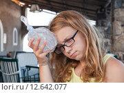 Девочка-подросток держит пластиковый мешок с льдом у головы, фото № 12642077, снято 16 августа 2015 г. (c) Евгений Сергеев / Фотобанк Лори