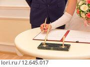 Купить «Регистрация брака, невеста с букетом цветов подписывает акт бракосочетания», фото № 12645017, снято 29 августа 2015 г. (c) Андрей С / Фотобанк Лори