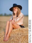 Девушка в ковбойской шляпе сидит на стоге сена. Стоковое фото, фотограф Дарья Швыдкая / Фотобанк Лори