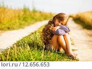 Девочка сидит на полевой дороге, обняв колени. Стоковое фото, фотограф Оксюта Виктор / Фотобанк Лори