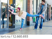 Купить «Smiling man trying to pull away his girlfriend from clothes store», фото № 12660693, снято 25 февраля 2015 г. (c) Wavebreak Media / Фотобанк Лори
