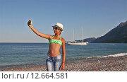 Купить «Девочка-подросток делает селфи на берегу средиземного моря», видеоролик № 12664581, снято 10 сентября 2015 г. (c) Мальцев Артур / Фотобанк Лори