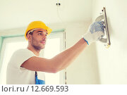 Купить «builder working with grinding tool indoors», фото № 12669593, снято 25 сентября 2014 г. (c) Syda Productions / Фотобанк Лори