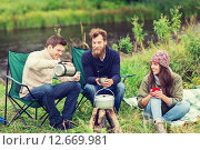 Купить «group of smiling tourists cooking food in camping», фото № 12669981, снято 31 августа 2014 г. (c) Syda Productions / Фотобанк Лори
