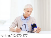 Купить «old woman with tonometer checking blood pressure», фото № 12670177, снято 10 июля 2015 г. (c) Syda Productions / Фотобанк Лори
