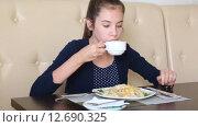 Купить «Девушка ест пасту и пьет кофе в кафе», видеоролик № 12690325, снято 7 сентября 2015 г. (c) Анна Балалаева / Фотобанк Лори