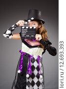 Купить «Pretty girl in jester costume holding clapperboard against gray», фото № 12693393, снято 11 сентября 2013 г. (c) Elnur / Фотобанк Лори
