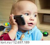 Купить «Мальчик (1 год и 3 месяца) с мобильным телефоном», эксклюзивное фото № 12697189, снято 7 сентября 2015 г. (c) Вячеслав Палес / Фотобанк Лори