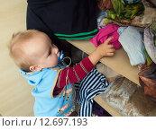 Купить «Мальчик (1 год и 3 месяца) достает вещи из шкафа», эксклюзивное фото № 12697193, снято 7 сентября 2015 г. (c) Вячеслав Палес / Фотобанк Лори