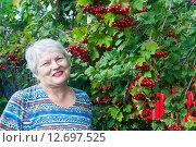 Купить «Довольная улыбающаяся женщина 70 лет на фоне калины, которую она вырастила сама», эксклюзивное фото № 12697525, снято 16 августа 2015 г. (c) Наталья Федорова / Фотобанк Лори