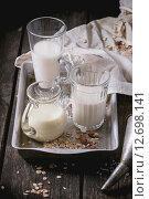 Купить «Набор немолочного молока (рисовое молоко, миндальное молоко и овсяное молочко) в стеклянной посуде на старом алюминиевом подносе», фото № 12698141, снято 8 сентября 2015 г. (c) Natasha Breen / Фотобанк Лори