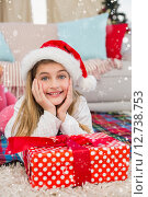 Купить «Composite image of festive little girl smiling at camera with gift», фото № 12738753, снято 10 июля 2020 г. (c) Wavebreak Media / Фотобанк Лори