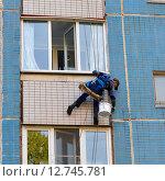 Промышленный альпинист закрашивает швы панельного многоэтажного дома. Стоковое фото, фотограф Наталья Горкина / Фотобанк Лори