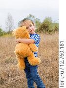 Маленькая девочка стоит на траве и обнимает плюшевого мишку. Стоковое фото, фотограф Вячеслав Волков / Фотобанк Лори
