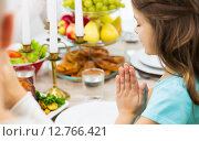 Купить «close up of girl praying at holiday dinner», фото № 12766421, снято 14 сентября 2014 г. (c) Syda Productions / Фотобанк Лори