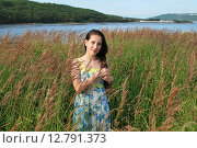 Купить «Портрет девушки на фоне травы», фото № 12791373, снято 23 августа 2015 г. (c) Ирина Здаронок / Фотобанк Лори