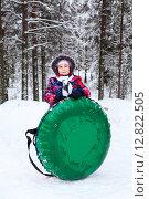 Купить «Девочка в зимней одежде стоит в лесу и держит надувную ватрушку для катания», фото № 12822505, снято 20 декабря 2014 г. (c) Кекяляйнен Андрей / Фотобанк Лори