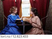 Купить «Two sisters in retro dress reading books in train compartment», фото № 12823433, снято 12 июля 2015 г. (c) Serg Zastavkin / Фотобанк Лори