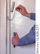 Мужчина снимает дверную цепочку. Стоковое фото, фотограф Виктор Колдунов / Фотобанк Лори